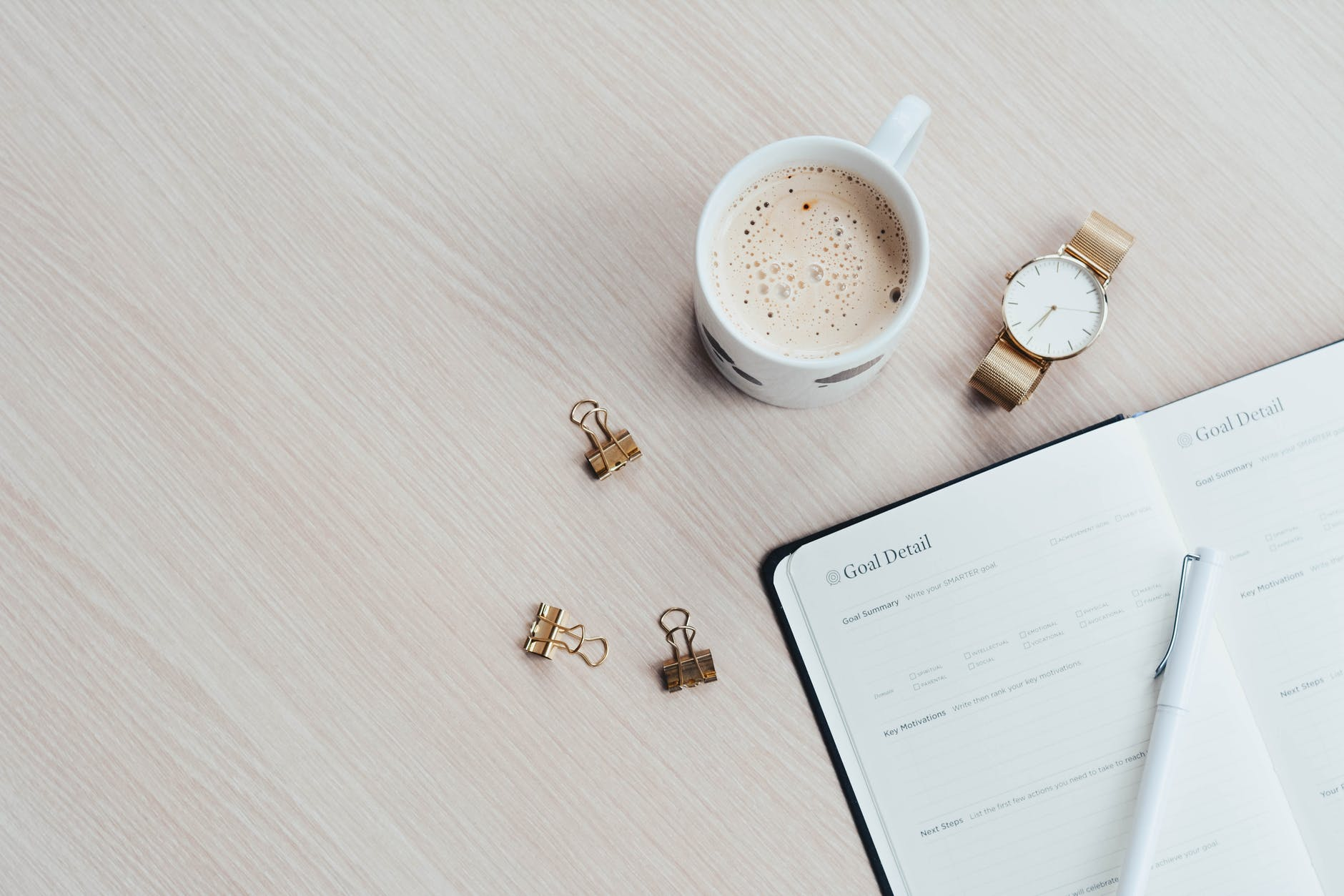 mug watch and planner book on brown wooden surface